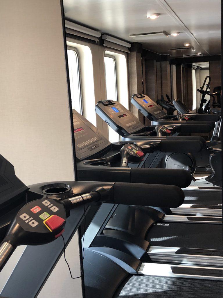 Der Fitness-Raum von World Explorer ist groß und hat Panorama-Fenster zum Außendeck